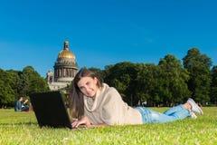 一棵草的少妇在公园或庭院使用膝上型计算机 库存照片