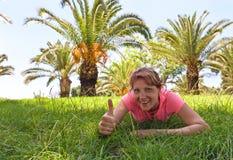 一棵草的愉快的妇女在有棕榈树的果树园 免版税库存图片