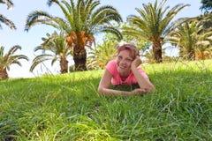 一棵草的愉快的妇女在有棕榈树的果树园 图库摄影