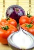 一棵整个蕃茄和被切的葱 免版税库存照片