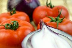 一棵整个蕃茄和被切的葱 免版税库存图片