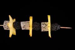 一棵水多的黄色阳桃、黑莓和龙在深黑色背景的一根木棍子结果实 樱桃手抓食物无盐干酪蕃茄 库存照片