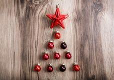 以一棵Xmas树的形式红色圣诞节装饰品在土气木背景 圣诞快乐看板卡 新年好 免版税库存图片
