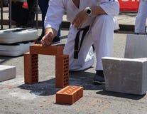 一次体育比赛的空手道球员打破一块砖用他的手 库存照片