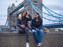 一次城市旅行的两个女孩向伦敦-放松在塔桥梁 库存照片
