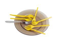 一次性叉子和一把不锈钢叉子在玻璃盘 免版税库存照片