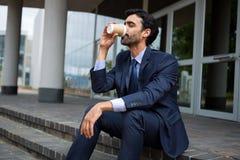 从一次性杯子的商人饮用的咖啡 免版税库存照片