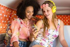 一次旅行的愉快的朋友使用听到音乐 免版税库存图片