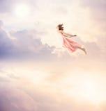 一次桃红色礼服飞行的女孩在天空 免版税图库摄影