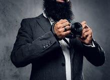 一次衣服射击的专业摄影师与一台紧凑DSLR照相机 免版税库存图片