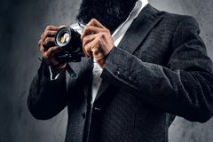 一次衣服射击的专业摄影师与一台紧凑DSLR照相机 免版税库存照片