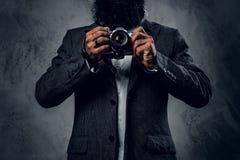 一次衣服射击的专业摄影师与一台紧凑DSLR照相机 库存照片