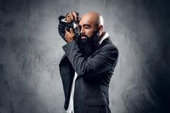 一次衣服射击的专业摄影师与一台紧凑DSLR照相机 免版税图库摄影