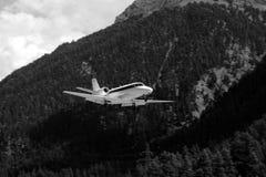 一次飞机飞行在天空中有森林山背景 库存图片