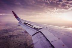 一次飞机飞行的翼在云彩上的在日落 (过滤器 图库摄影