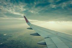 一次飞机飞行的翼在云彩上的在日落 (过滤器 库存照片