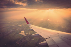 一次飞机飞行的翼在云彩上的在日落 (过滤器 库存图片