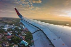 一次飞机飞行的翼在云彩上的在日落 (过滤器 免版税库存照片