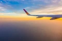 一次飞机飞行的翼在云彩上的在日落 图库摄影
