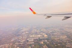 一次飞机飞行的翼在云彩上的在日落 免版税图库摄影