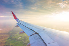 一次飞机飞行的翼在云彩上的在日落 库存照片