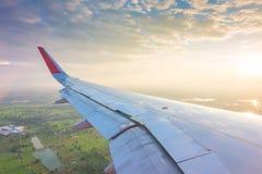 一次飞机飞行的翼在云彩上的在日落 库存图片