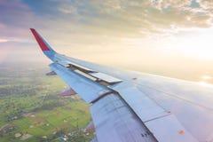 一次飞机飞行的翼在云彩上的在日落 免版税库存图片