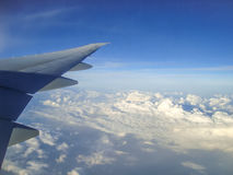 一次飞机飞行的翼在云彩上的在蓝天 库存图片