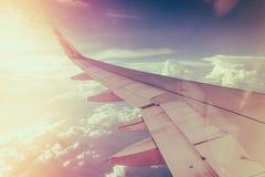 一次飞机飞行的翼在云彩之上的 (被过滤的图象PR 库存照片