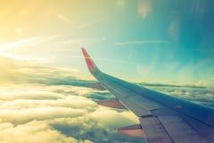 一次飞机飞行的翼在云彩之上的 (被过滤的图象PR 免版税库存照片
