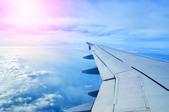 一次飞机飞行的翼在云彩之上的 免版税库存图片