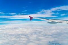 一次飞机飞行的翼在云彩之上的 库存照片