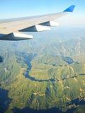 一次飞机飞行的翼在山上的 飞机背景概念地球例证查出surranded移动的白色 照片被应用于旅游业操作员 免版税库存图片