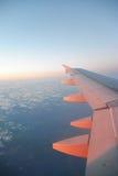 一次飞机飞行的翼在日出上的覆盖 免版税图库摄影