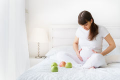 一欧洲怀孕的wooman坐白色接触她的腹部的床用三个绿色苹果和smilng在卧室 免版税库存图片