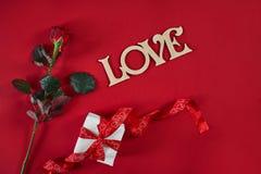 一深红上升了与红色丝带和礼物盒在红色背景 浪漫华伦泰假日概念 日s华伦泰 免版税库存图片