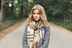 一温暖围巾和外套走的美丽的时髦的少妇 免版税库存照片