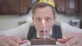 一滑稽的年轻人的被弄脏的画象坐在一个小巧克力蛋糕前面的生日帽子的在厨房里 ?treadled 股票视频