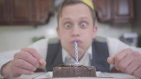 一滑稽的愉快的年轻人的画象吹灭在一个小巧克力蛋糕的生日帽子的蜡烛在厨房里 ?treadled 股票录像