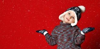 一点一个帽子有大型机关炮和手套的,胳膊被伸出对边和抓住雪花的逗人喜爱的男孩 库存照片