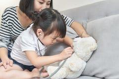 一点与娃娃玩具的亚洲女孩戏剧 小的亚洲女孩举行听诊器在手中和检查娃娃玩具 免版税库存图片