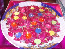 一点与玫瑰色叶子的五颜六色的蜡烛光 库存照片