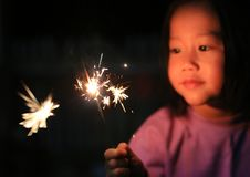 一点亚裔儿童女孩喜欢演奏爆竹 在火闪烁发光物的焦点 免版税库存图片