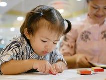 一点亚裔女婴单独与蜡笔,当她的忽略她和单独地集中于智能手机时的母亲 库存图片