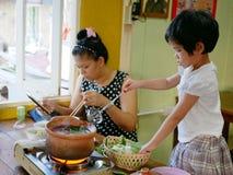 一点亚裔女婴喜欢烹调她的母亲的一火锅 免版税库存图片