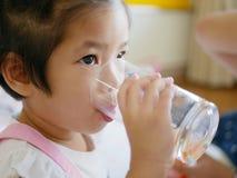 一点从玻璃/杯子的亚洲女婴饮用水由她自己 免版税图库摄影