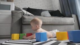 一点使用与一个建设者的五颜六色的小块的男婴在地板上的屋子里 使用与上色的孩子 股票录像