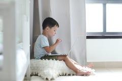 一点使用膝上型计算机的逗人喜爱的男孩在舒适屋子 免版税库存照片
