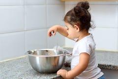 一点做蛋糕面包店的小孩女孩在厨房里 免版税库存照片