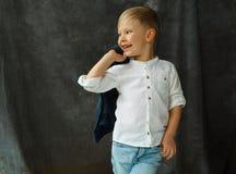 一点兴高采烈的俏丽的男孩画象牛仔裤的在灰色纺织品 库存图片